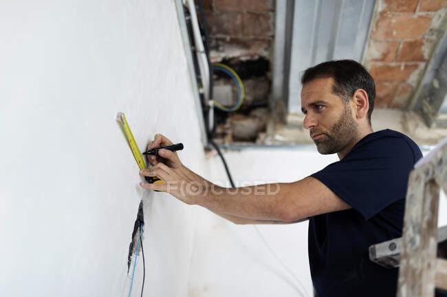 Працівник будівельних робіт, що відзначає стіну. — стокове фото