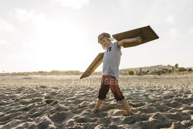 Niño con alas de avión y gorra mientras está de pie con los brazos extendidos en la playa - foto de stock
