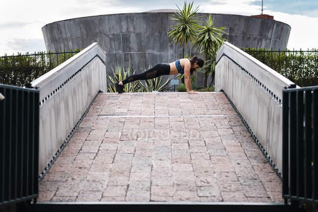Молодая женщина во время тренировки на мосту — стоковое фото