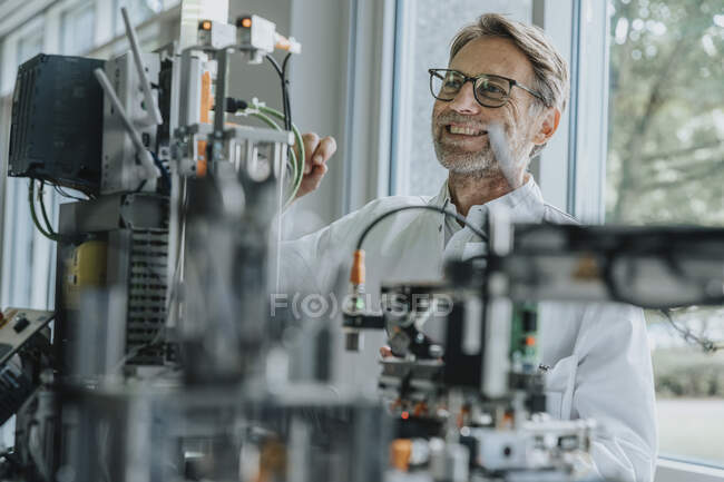 Smiling male technician examining machinery in laboratory — Stock Photo