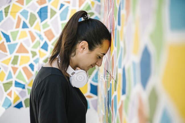 Retrato de mujer con auriculares blancos frente a la pared colorida - foto de stock