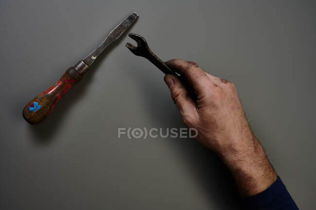 Top view of hand with tools in front of grey background — Stock Photo