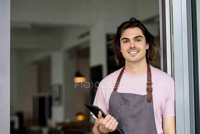 Усміхаючись чоловік, який тримає цифрову табличку, стоячи біля входу в кав