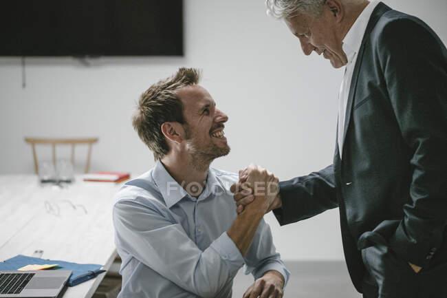 Старший бізнесмен Шакінг, руки молодшого ділового партнера. — стокове фото