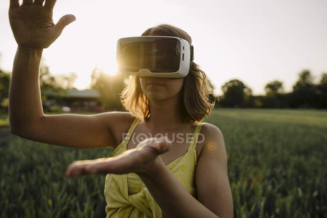 Mujer joven con gafas VR en un campo de grano en el campo - foto de stock
