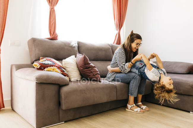 Happy mother and daughter playing on sofa at home — стоковое фото