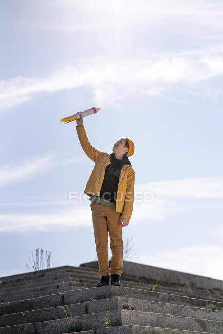 Niño sosteniendo cohete juguete mientras está de pie en los pasos contra el cielo - foto de stock