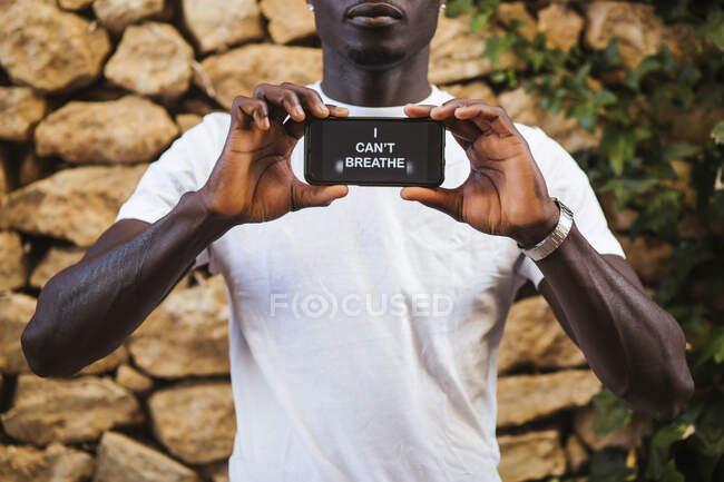 Крупный план молодого человека, показывающего текст по смартфону у каменной стены — стоковое фото
