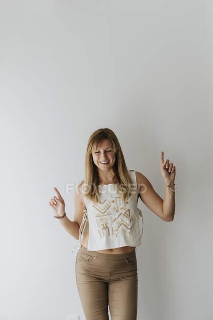 Mujer sonriente bailando contra la pared blanca en casa - foto de stock