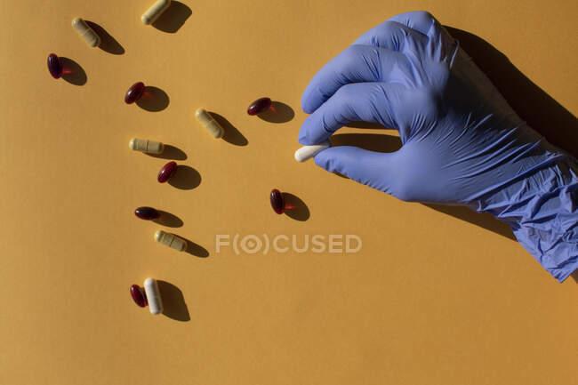 Рука з хірургічною рукавичкою кладе капсули. — стокове фото