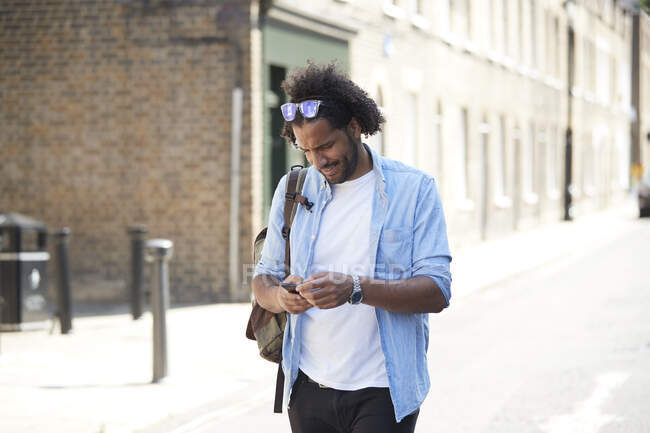 Young man with backpack standing on street looking at cell phone, London, UK — Foto stock