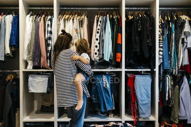 Mãe carregando filha ao escolher roupas no camarim em casa — Fotografia de Stock