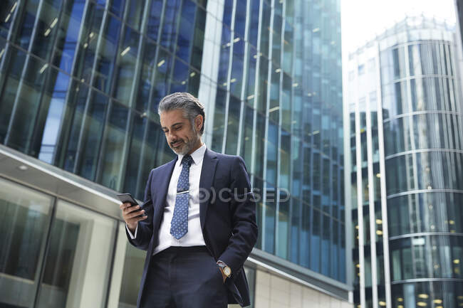 Businessman using mobile phone outside office building in city — стокове фото
