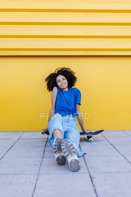 Smiling young woman sitting on skateboard in front of yellow wall — стокове фото
