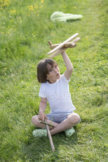 Играющий мальчик летит моделью самолета, сидя на травянистой земле — стоковое фото
