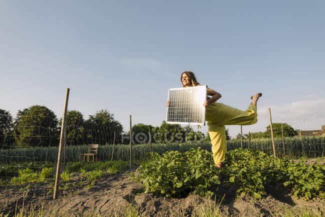 Молода жінка стоїть у овочевому клапті в сільській місцевості і тримає сонячну панель. — стокове фото