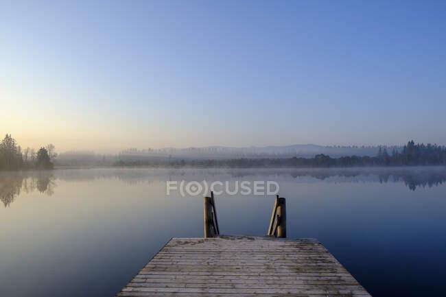 Una ragazza sola si trova sulla riva di un lago calmo con il sole e la nebbia mattutina sul — Foto stock