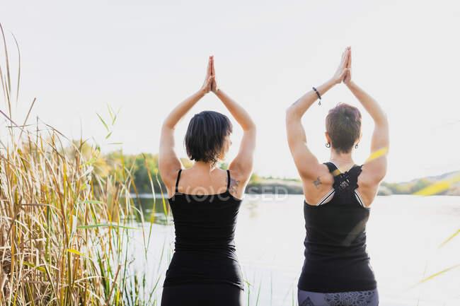 Женщины-подруги с поднятыми руками, тренирующиеся на озере на ясном небе — стоковое фото