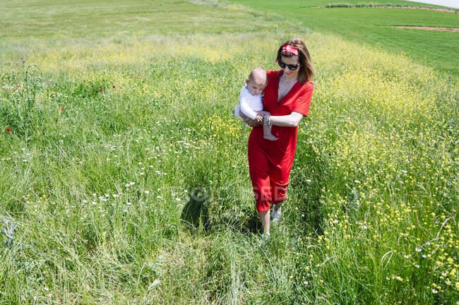 Madre llevando a su hijo bebé mientras camina en tierra herbosa durante el día soleado - foto de stock