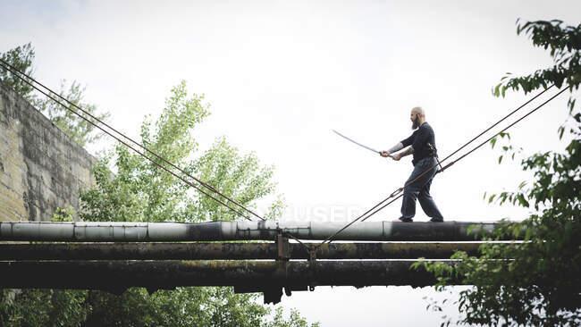 Лысый мужчина держит меч позируя, стоя на старых трубах против ясного неба — стоковое фото