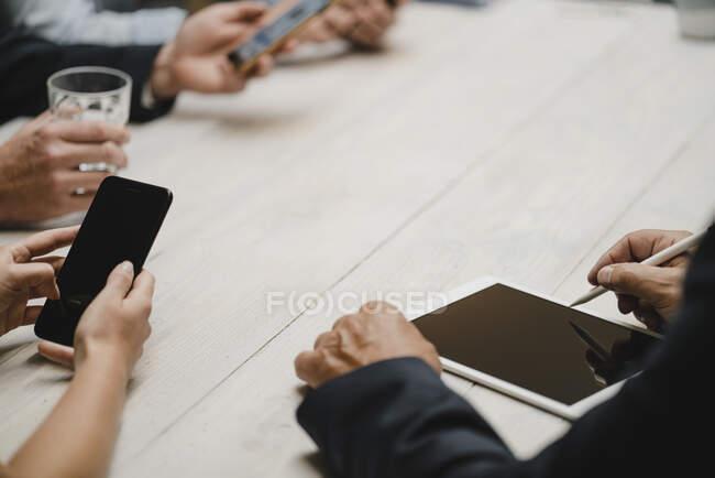 Gente de negocios que trabaja en la oficina usando dispositivos portátiles, de cerca - foto de stock