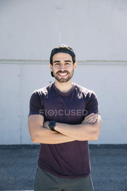 Confident mid adult man with arms crossed standing against wall in city — Stock Photo