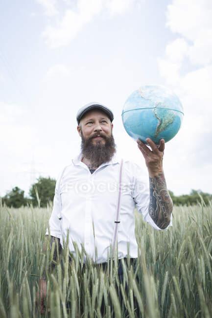 Одягнена людина тримає глобус, озираючись, стоячи посеред кукурудзяного поля проти неба. — стокове фото