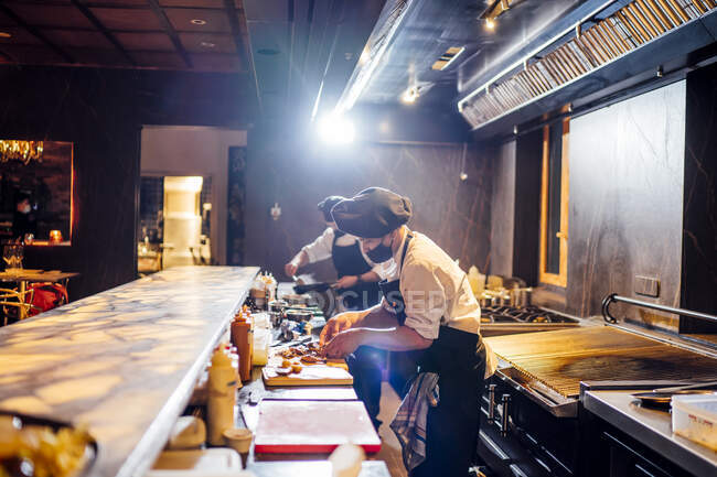 Chefs wearing protective face masks preparing a dish in restaurant kitchen — Stock Photo