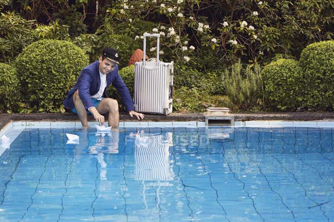 Uomo galleggiante barche di carta sulla piscina mentre seduto con valigia contro le piante in cortile — Foto stock