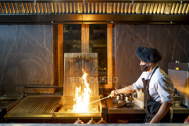 Chef wearing protective face mask preparing grill in restaurant kitchen — Stock Photo