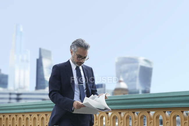 Businessman reading paper against clear sky in city — стокове фото