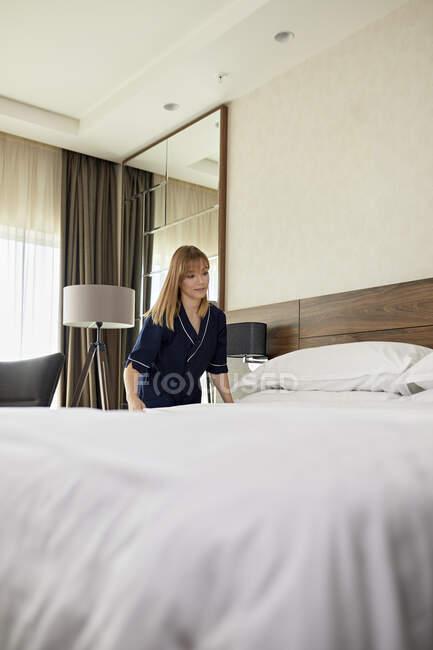 Camarera haciendo cama en habitación de hotel - foto de stock