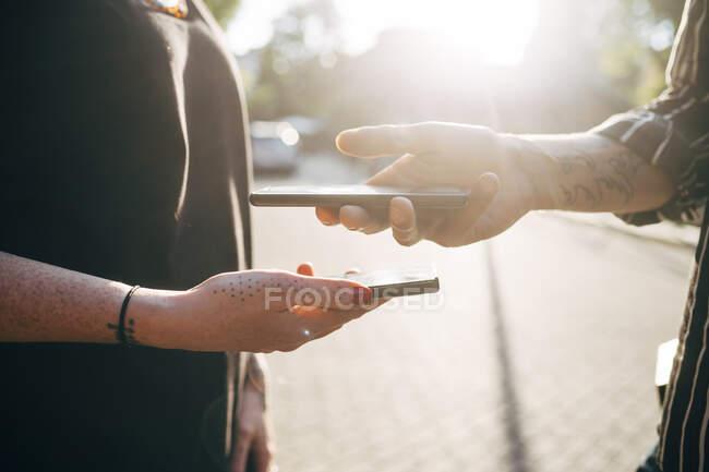 Primer plano del código de escaneo de pareja a través de teléfonos inteligentes en la ciudad durante el día soleado - foto de stock