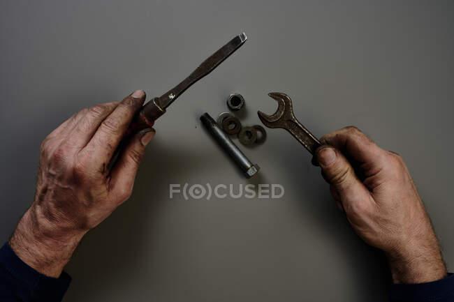 Верхній вид рук з інструментами перед сірим фоном. — стокове фото