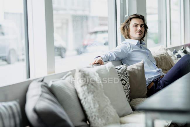 Уверенный бизнесмен отдыхает на диване у окна в кафе — стоковое фото