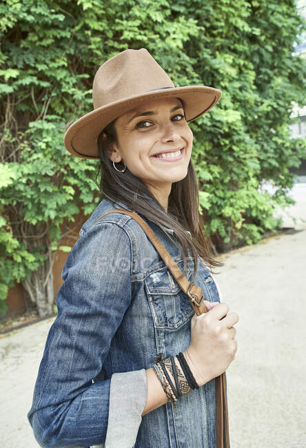 Happy woman wearing sun hat and denim jacket while standing on footpath during sunny day — Stock Photo