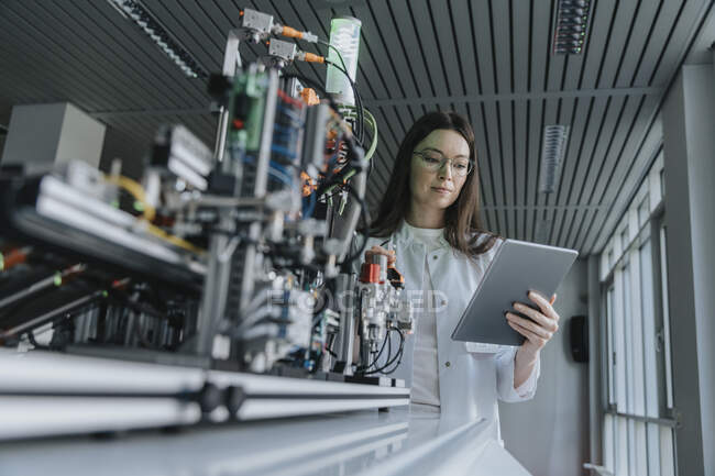 Young woman using digital tablet while standing by machinery in laboratory — Stock Photo