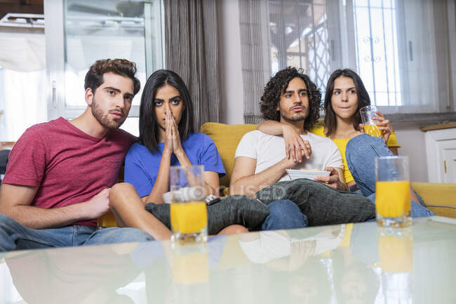 Young multi-ethnic friends in stress watching TV at home — стоковое фото
