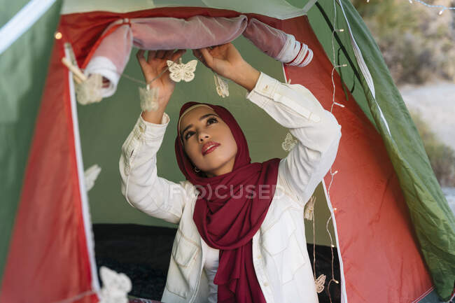 Young tourist woman wearing Hijab decorating a tent — Photo de stock