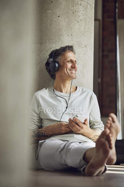 Улыбающийся мужчина в наушниках слушает музыку в квартире на чердаке — стоковое фото