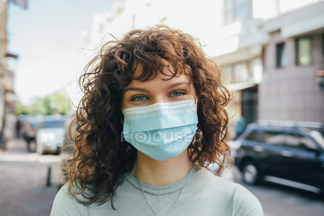 Brunette curly woman wearing protective mask in city - foto de stock