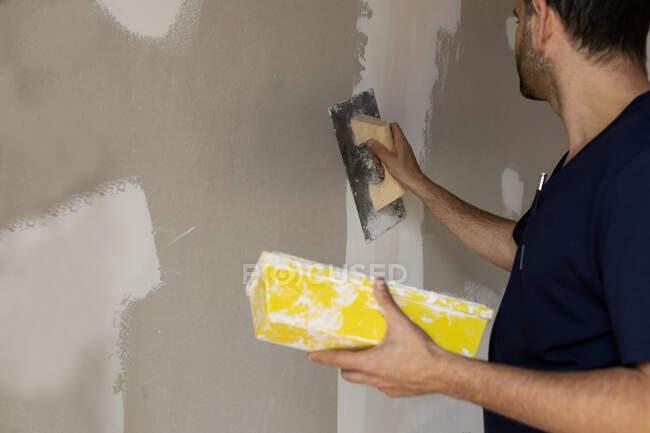 Працівник будівельних робіт, що штукатурує стіну в домі. — стокове фото