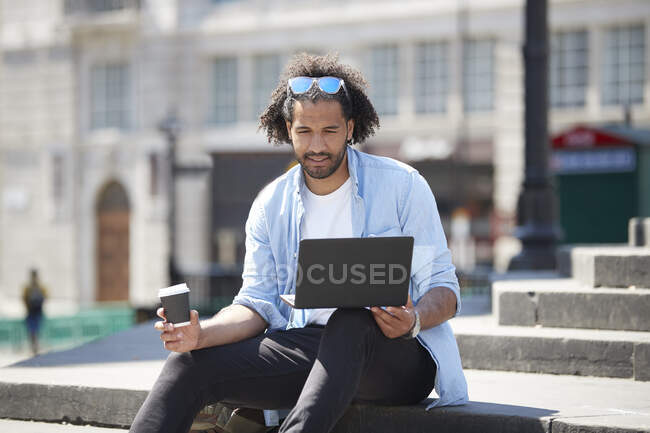 Portrait of young man with coffee to go sitting on stairs outdoors looking at laptop, London, UK — Foto stock