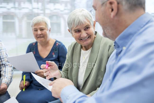 Пожилые люди в группе терапии в доме престарелых записывают заметки на листах бумаги — стоковое фото