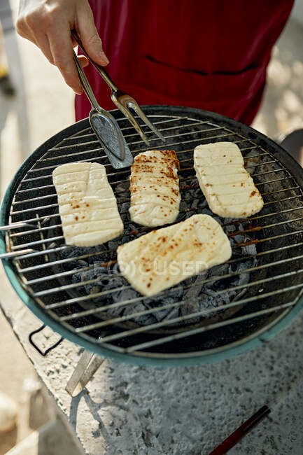 Cropped shot of man cooking Halloumi cheese on barbecue grill — Stock Photo