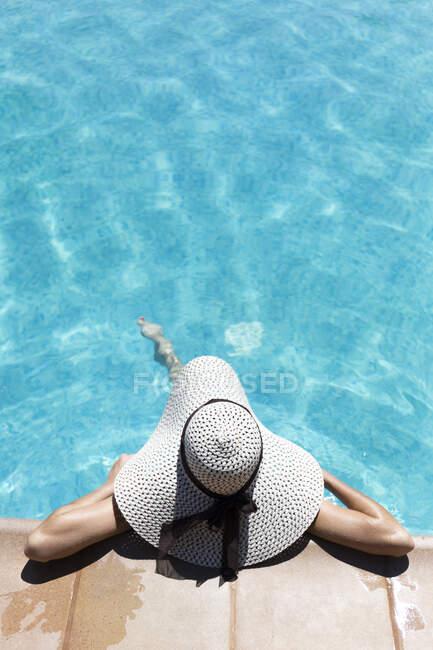 Mujer joven con sombrero relajante en la piscina en el complejo turístico durante el día soleado - foto de stock