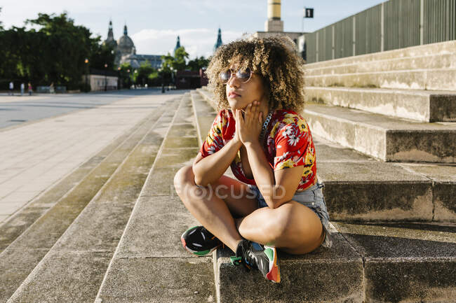 Thoughtful trendy woman sitting on steps in city — Stock Photo