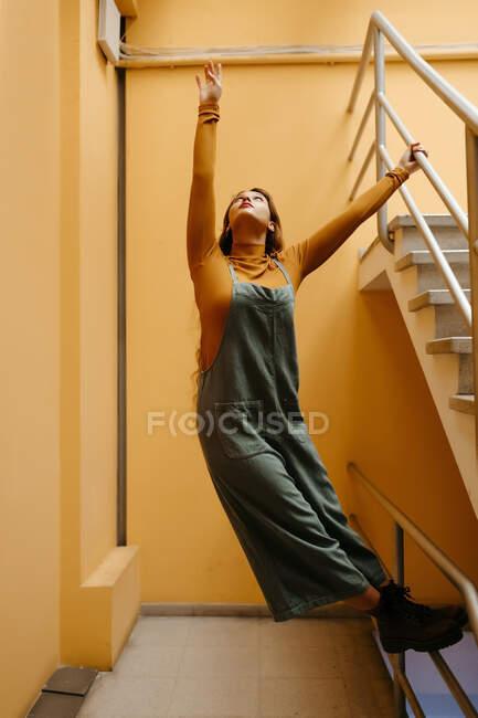 Молодая женщина в комбинезоне стоит на перилах перед оранжевой стеной — стоковое фото