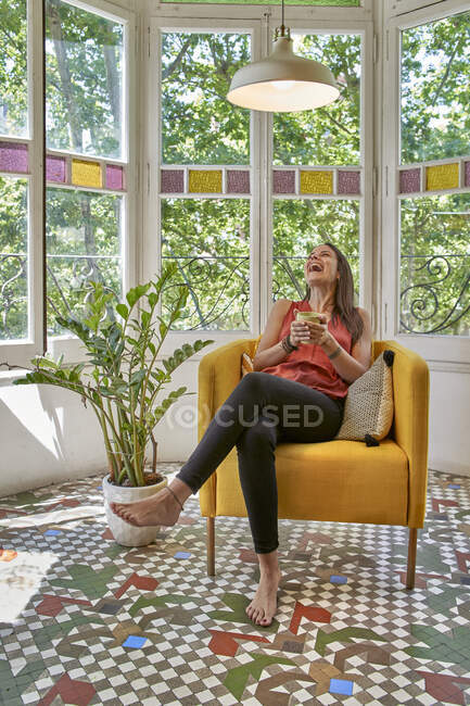 Cheerful woman with cup sitting on armchair against window at home — Stock Photo