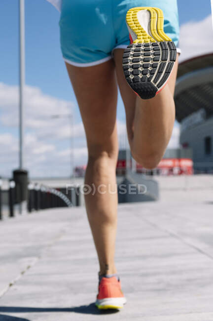 Legs of mid adult woman running on sidewalk in city during sunny day — Stock Photo